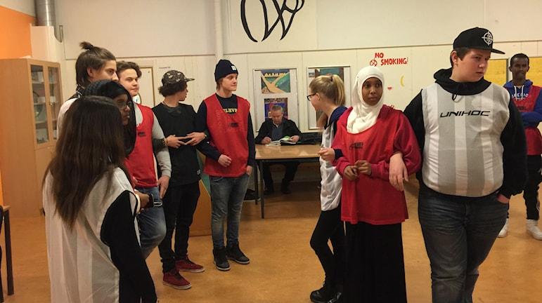 Elever i svarta, vita och röda västar iscensätter vatten och koldioxid. Foto: Carin Vidner/Sveriges Radio.