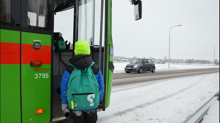 Ett barn är på väg att kliva på bussen vid snöig landsväg. Foto: Petra Levinson/Sveriges Radio.