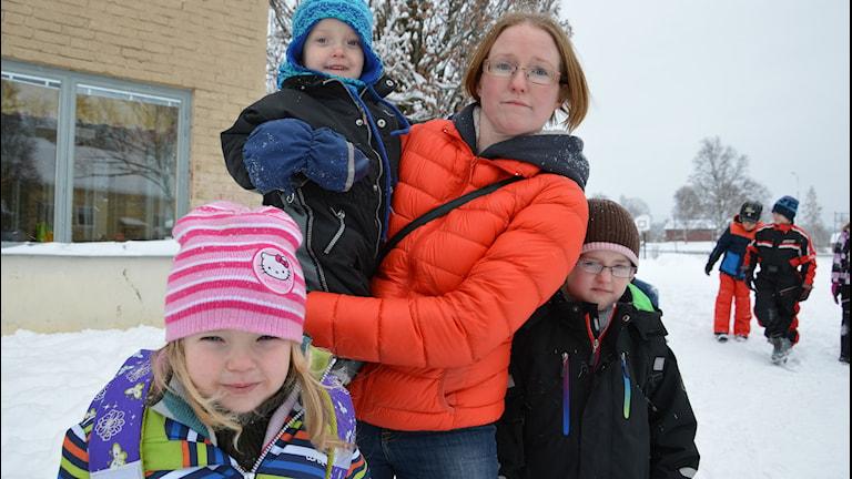 Monica Vigren på snötäckt skolgård tillsammans med barnen My, Moltas och Alma Vigren. Foto: Petra Levinson/Sveriges Radio.