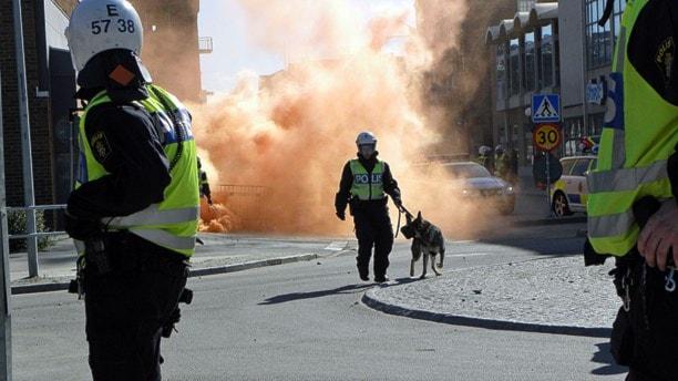 Poliser rusar fram i stadsmiljö. Bakgrund: rök från rökbomb. Foto: Michael Berwick/Sveriges Radio.