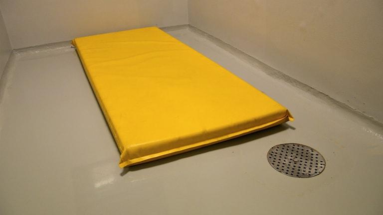 En gul madrass och en golvbrunn i ett grått, kalt rum. Foto: Petra Levinson/Sveriges Radio.