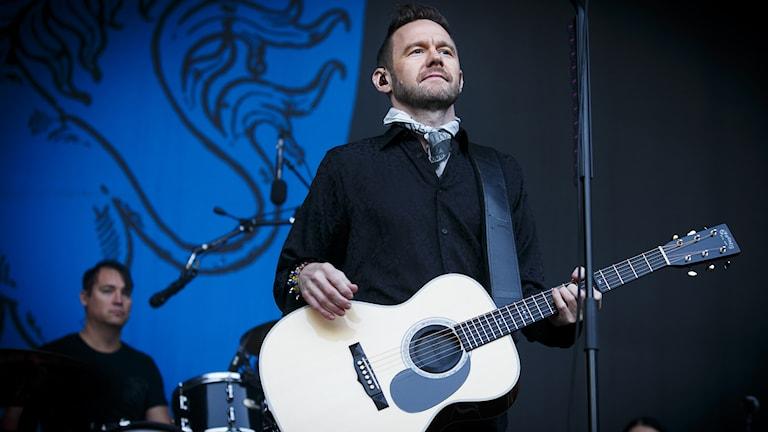 Joakim Berg med akustisk gitarr på magen. Foto: Heiko Junge/TT