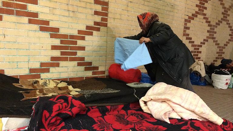 En kvinna med sjalett bäddar två madrasser vid en tegelvägg. Foto: Petra Levinson/Sveriges Radio.