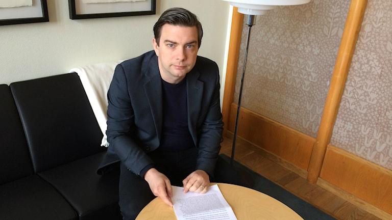 Jimmy Jansson med ett papper framför sig på ett bord. Foto: Petra Levinson/Sveriges Radio.