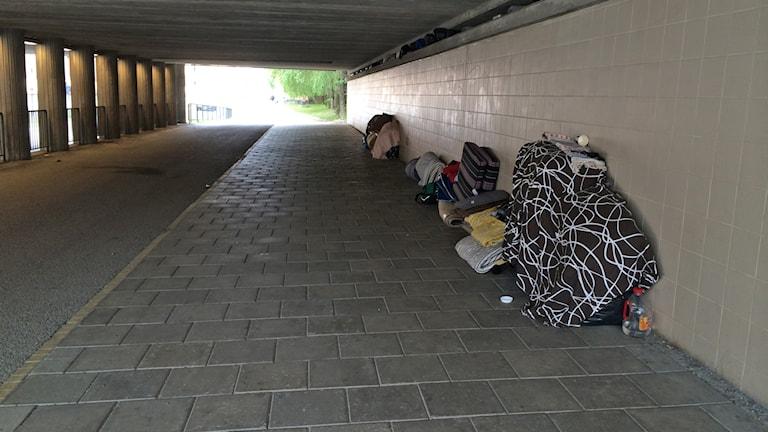 En tunnel med täcken och hoprullade madrasser utmed väggarna. Foto: Petra Levinson/Sveriges Radio.