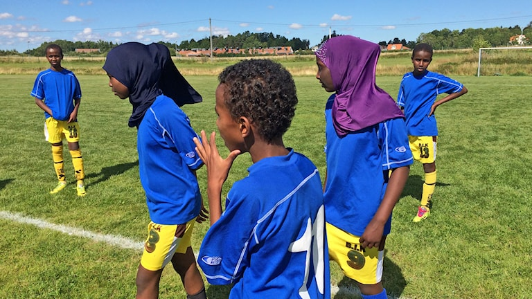Fem barn i matchkläder på en fotbollsplan, två flickor med huvudduk. Foto: Petra Levinson/Sveriges Radio.