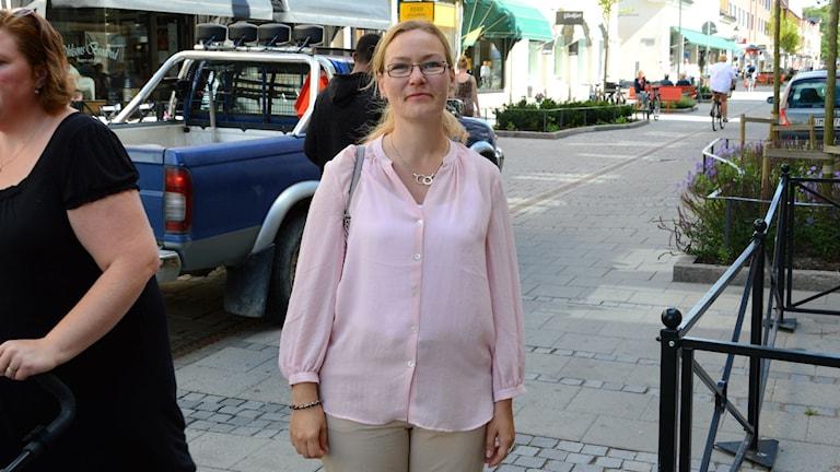 Malin Hagerström, Miljöpartistiskt kommunalråd i Nyköping, på Östra Storgatan med bil bakom ryggen. Foto: Urban Hedqvist/Sveriges Radio