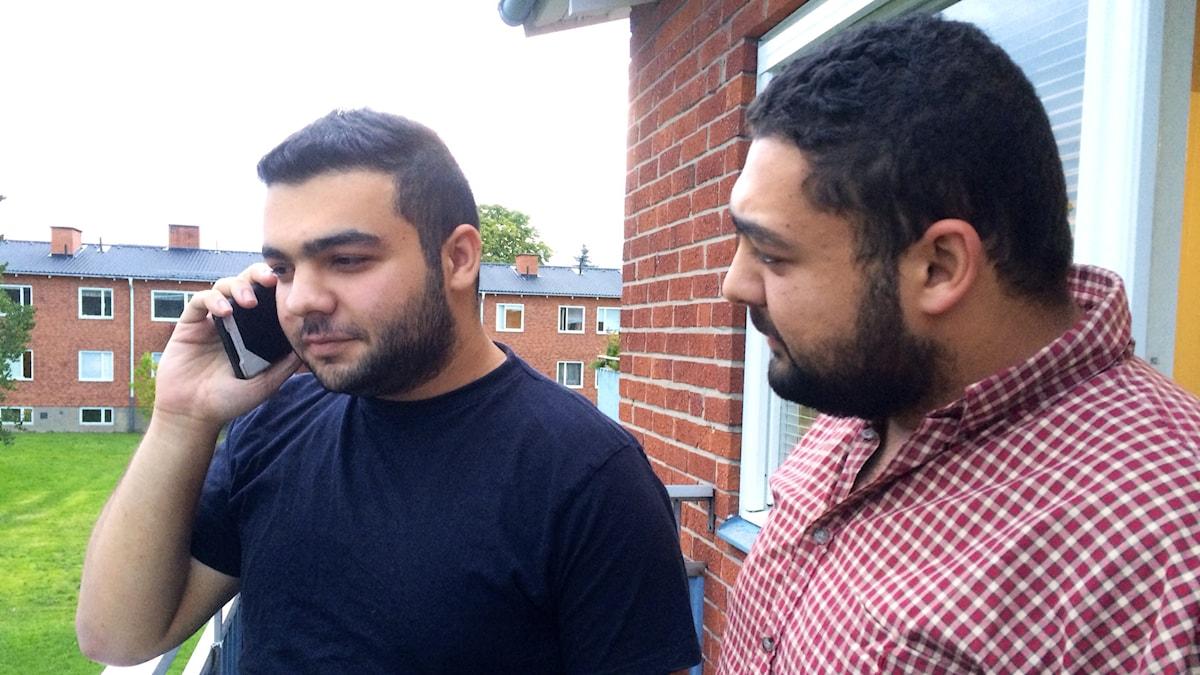 Bröderna Majd och Anas står och pratar i mobilen på en balkong.  Foto: Petra Levinson/Sveriges Radio.