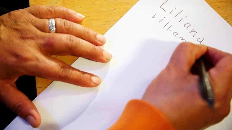 Någon skriver sitt namn på ett papper. Foto: Fredrik Persson/TT.
