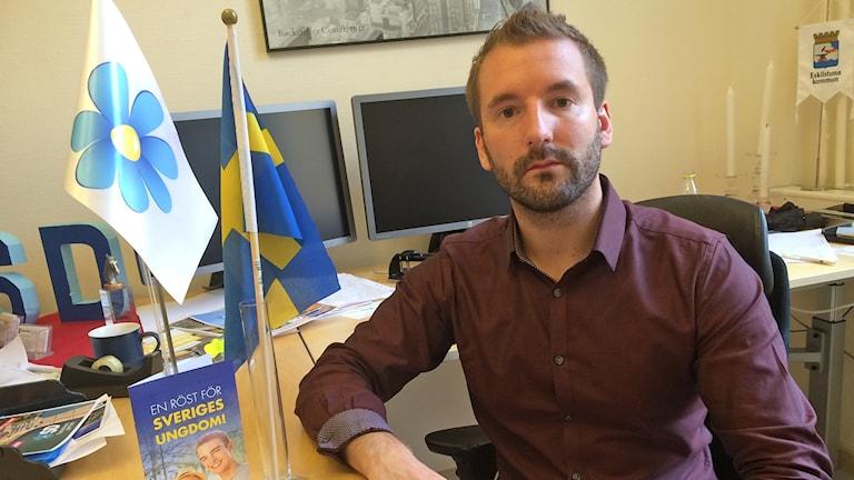 Kim Fredriksson med en SD-flagga och en svensk flagga bredvid sig på skrivbordet. Foto: Petra Levinson/Sveriges Radio.
