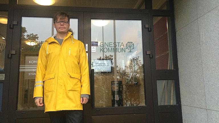 Mikke Schirén står i gul regnkappa utanför kommunhuset i Gnesta. Foto: Annizeth Åberg