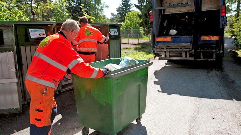 Två män i orange overaller tömmer sopor. Foto: Bertil Ericson/TT.