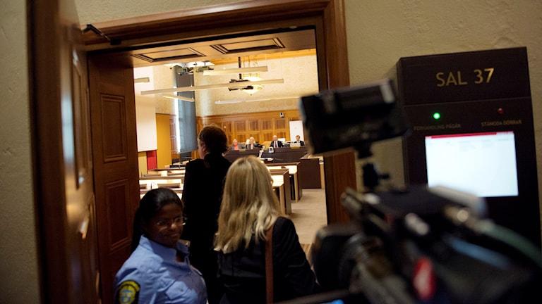 Två personer går in i en rättssal, en polis vaktar vid dörren. Foto: Jessica Gow/TT.