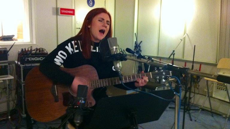 Josephine Thunell från Eskilstuna spelar på sin gitarr och sjunger framför en mikrofon Foto: Johanna Jennische/Sveriges Radio