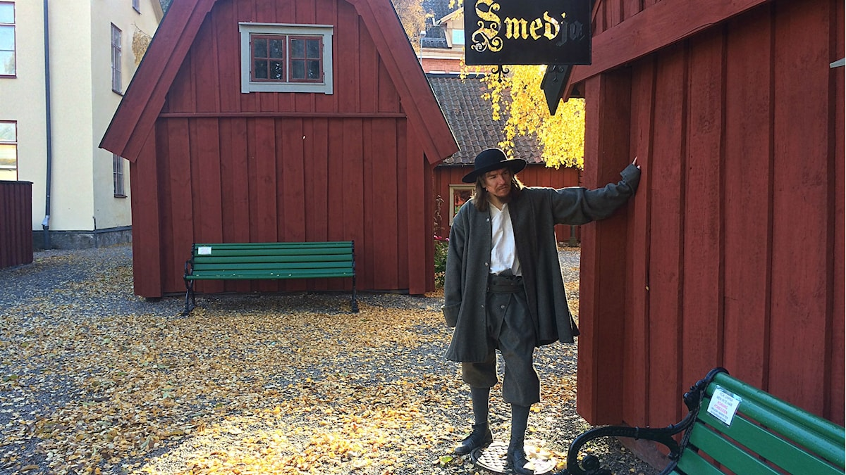 Dennis Malinovskiij Karlsson gestaltar smedjegesällen Daniel Schultz som levde på 1600-talet i Eskilstuna. Iförd yllekläder och hatt står han vid smedjan på Radermachergatan. Foto: Annizeth Åberg/Sveriges Radio