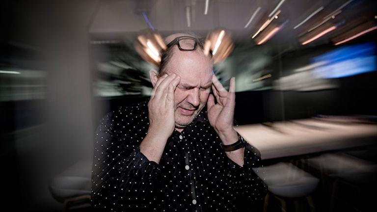 En man har ont i huvudet. Foto: Thomas Winje Øijord/TT.