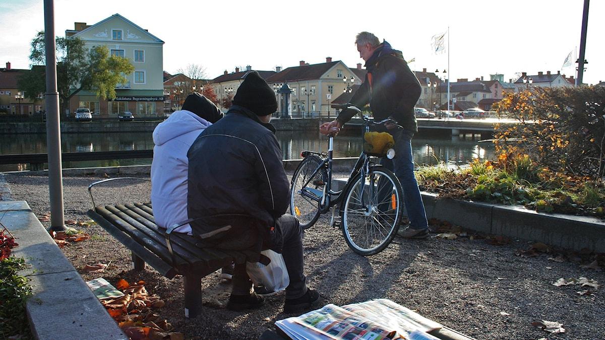 Två personer i tjocka jackor och mössor på en bänk vid ån. Foto: Petra Levinson/Sveriges Radio.