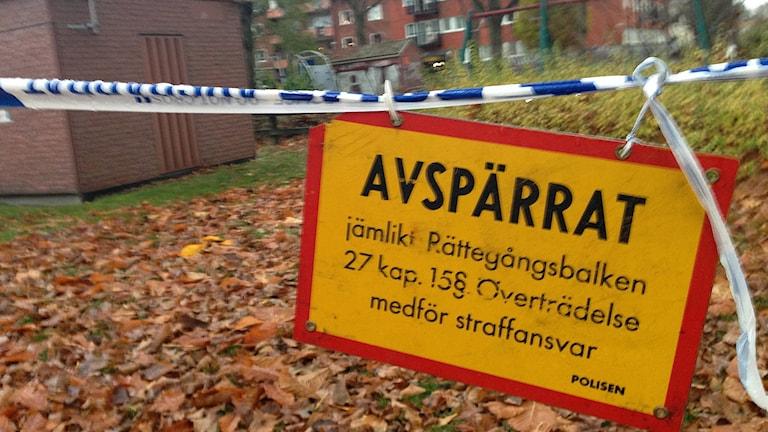Avspärningsband från polisen och en gul och röd varningsskylt med budskap om avspärrning. Foto: Ludvig Drevfjäll/Sveriges Radio.