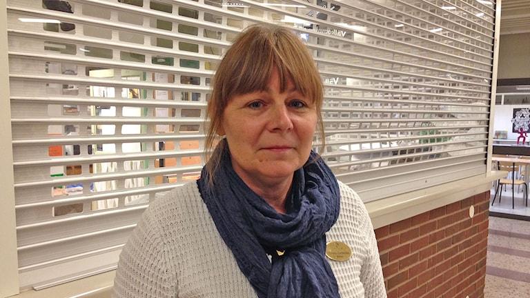 Rektor Helena Carlström på Rekarnegymnasiet i vit tröja med blå scarf. Foto: Evelina Crabb/Sveriges Radio.