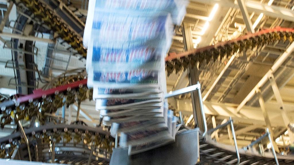Tidningar hänger på en ställning i ett tryckeri. Foto: Bertil Enevåg Ericson.