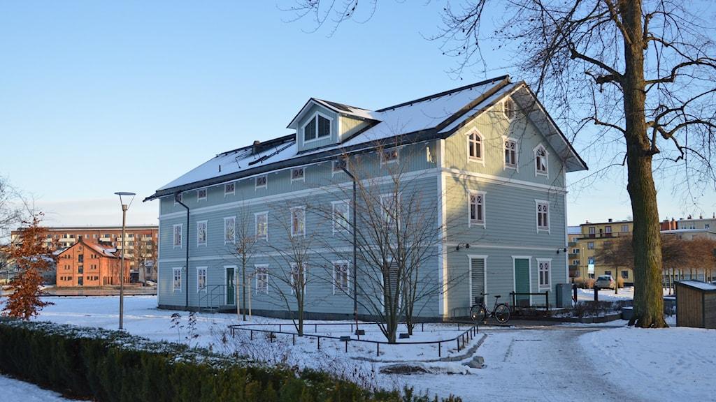 En ljusgrön träbyggnad i tre våningar, med snö på taket. Foto: Petra Levinson/Sveriges Radio.