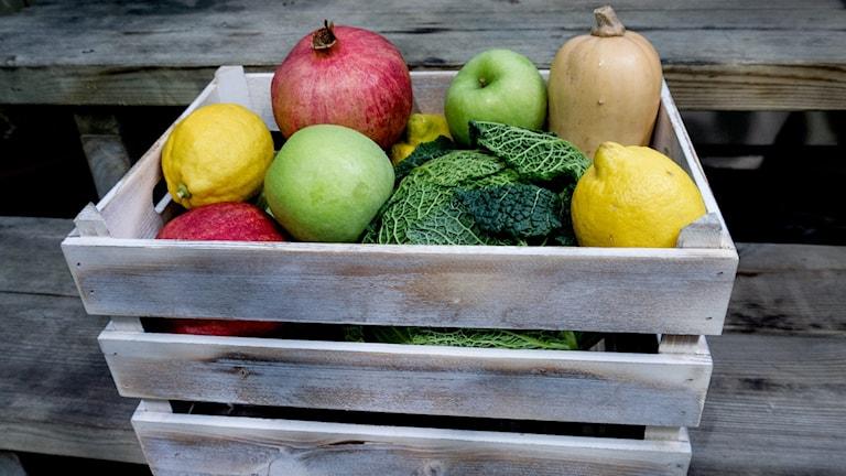 Klimatsmarta råvaror som exempelvis citron, äpple och savoykål i en trälåda. Foto: Malin Randeneyie