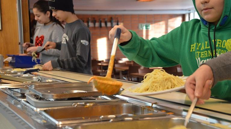 Skolelever lägger upp spaghetti och en orangefärgad sås på tallrikar i en skolbespisning. Foto: Petra Levinson/Sveriges Radio.