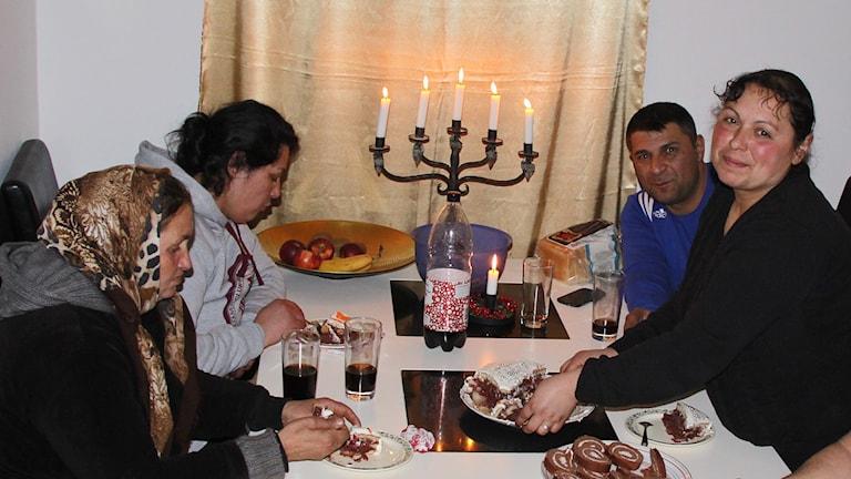 Mariana, Felicia, Jonut och Graciela äter tårta vid ett bord med tända ljus. Foto: Privat.