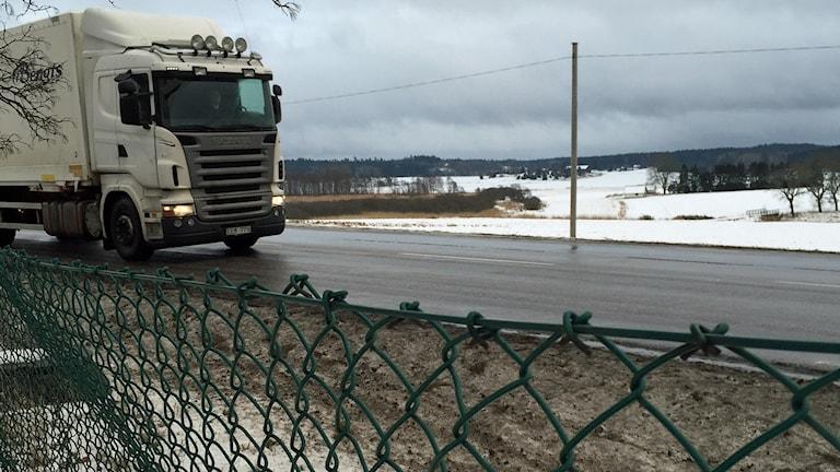 I förgrunden ett stängsel, på andra sidan en långtradare på väg förbi i ett vinterlandskap.