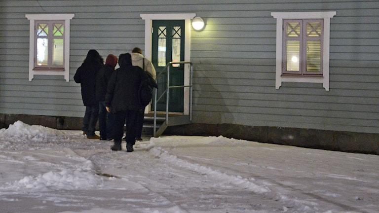 Fyra personer med uppdragna luvor köar vid ett trähus omgivet av snö. Foto: Petra Levinson/Sveriges Radio.