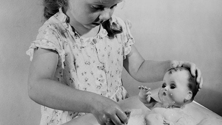 Flicka badar en docka.