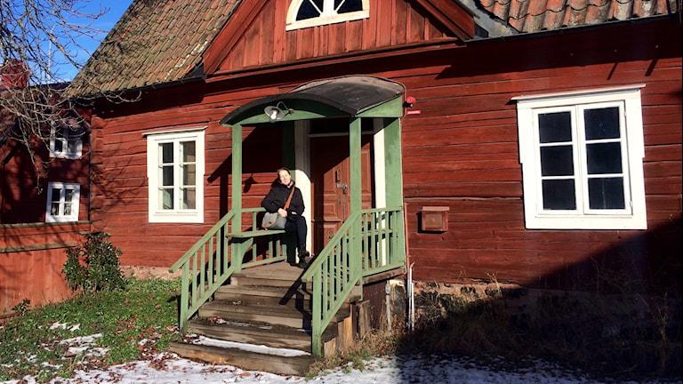 Anna Götzlinger sitter på en bänk på trappen till ett gammalt Fristadshus. Foto: Annizeth Åberg/Sveriges Radio