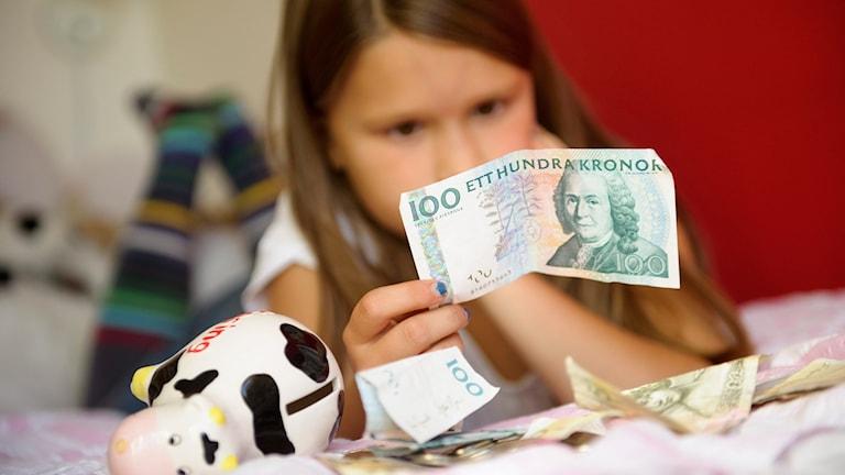 Flicka med pengar. Oklart om någon flyktingar har med pengarna på bilden att göra.
