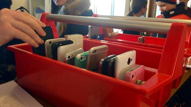 Röd låda med mobiler i.