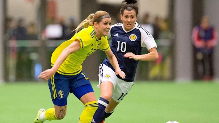 Sveriges Olivia Schough och Leanne Chrichton jagar boll vid en landskamp i fotboll mellan Sverige och Skottland på inomhusarenan Prioritet Serneke Arena i Göteborg. Foto: Björn Larsson Rosvall/TT.