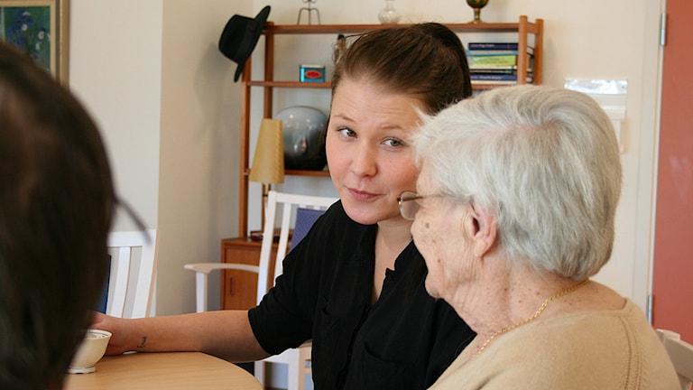 Lina Berggren pratar med en äldre kvinna vid ett fikabord. Foto: Petra Levinson/Sveriges Radio.