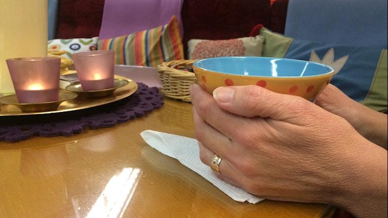 Händer håller i en färglad kopp.
