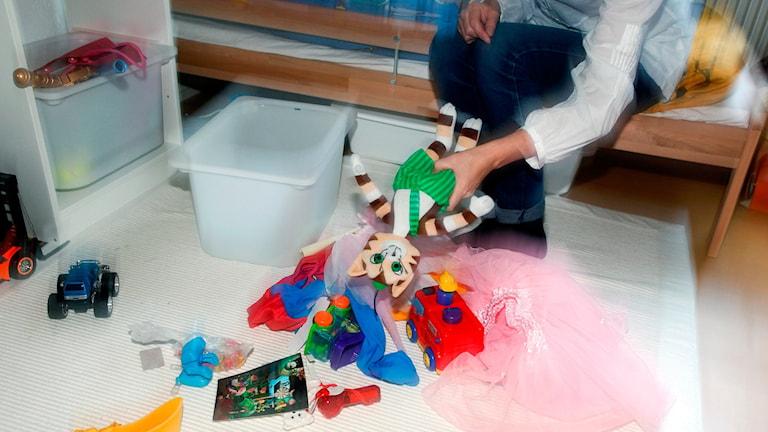 Vuxen plockar upp leksaker i barnrum.
