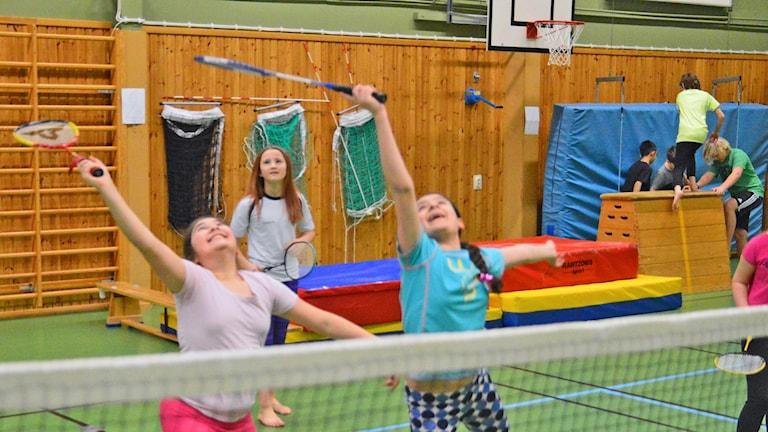 Tre barn spelar badminton i en gympasal, i bakgrunden några barn som klättrar på en plint. Foto: Petra Levinson/Sveriges Radio.