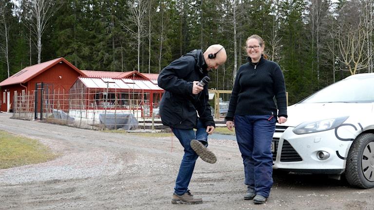 Urban Hedqvist, kollar in sin leriga sko, tillsammans med trädgårdsdesignern Helena Åhlund framför hennes trädgårdsanläggning.