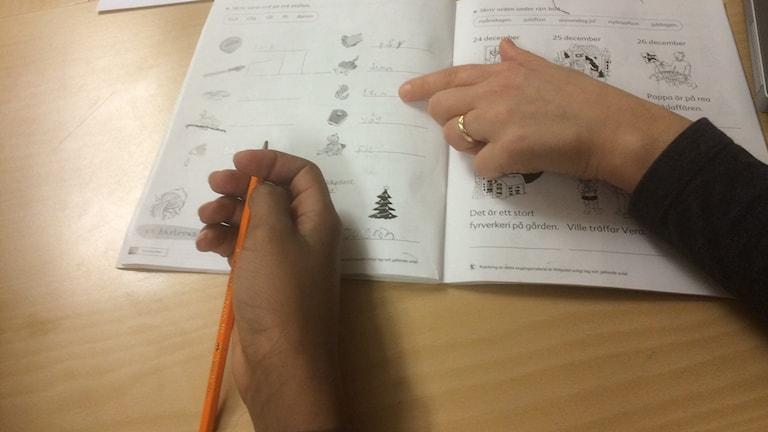 En elevs hand och en lärares hand pekar i en bok.