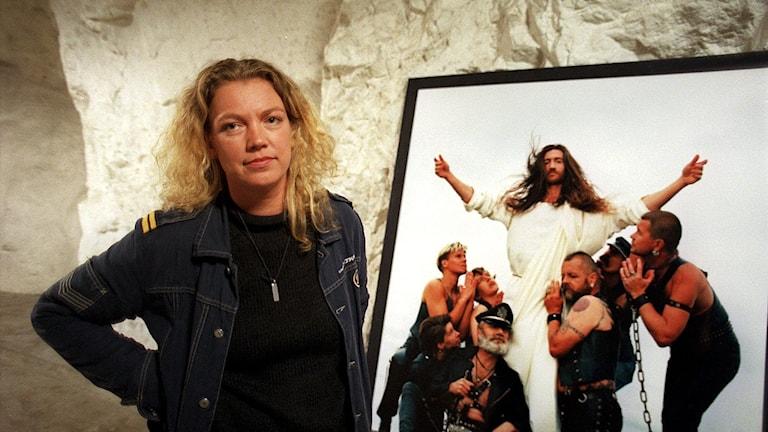 Fotoutställningen Ecce Homo. Utställning i ett bergrum på Södermalm i Stockholm av fotografen Elisabeth Ohlson. Här, juli 1998, ses hon vid en av sina fotografier. Foto: Ingvar Svensson/TT.