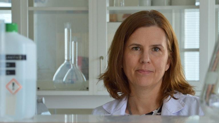 Christina Ödman bland glasflaskor i ett laboratorium.