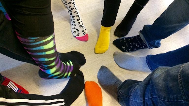 Elever från särskolan Pilen står i ring med färgglada strumpor på fötterna.