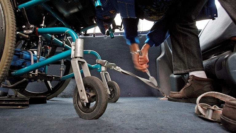 En rullstol spänns fast i en färdtjänstbil.