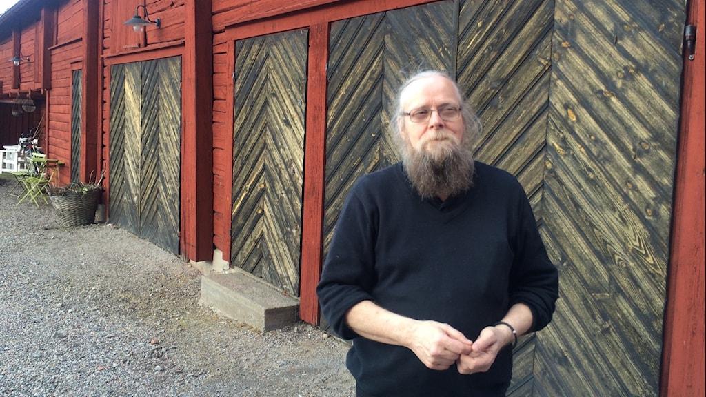 Håkan Sandvik står på en grusgård med gamla röda hus.