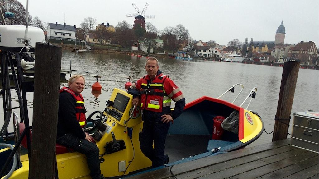 Sjöräddarna Pär och Lars står med flytvästar i räddningsbåten i hamnen.