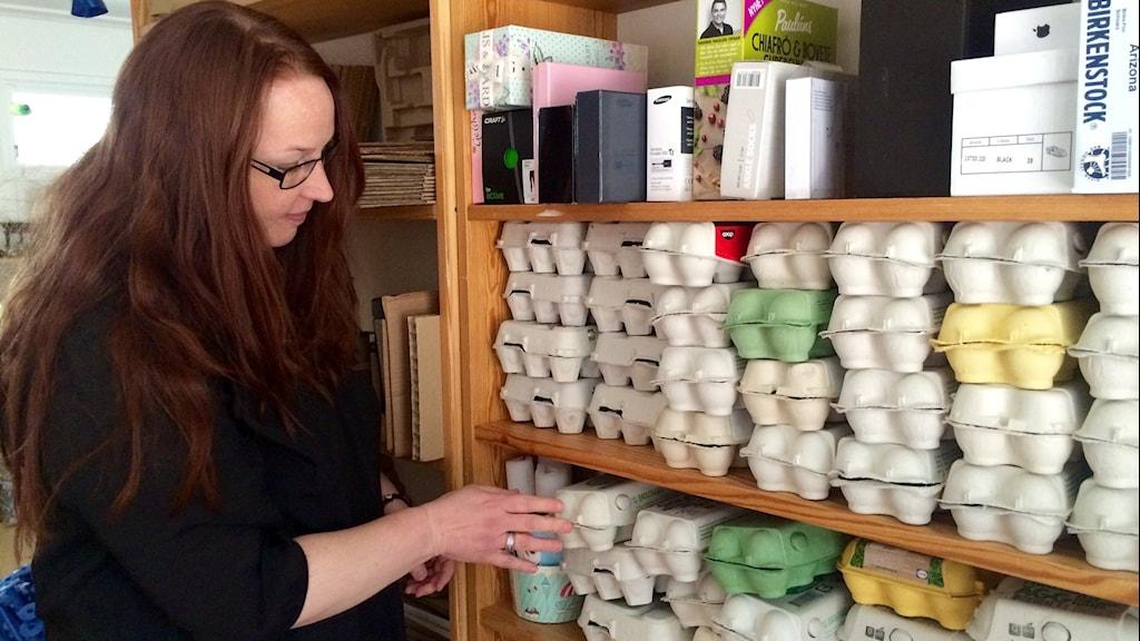 Sarah Näsström bläddrar bland äggkartonger i olika färger.
