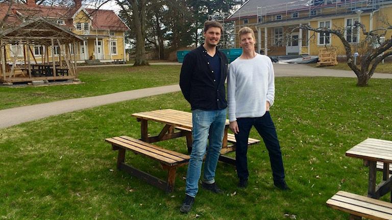 Peter Leisborn och Jan Jonsson står på gräsmattan mellan två gamla gula hus.