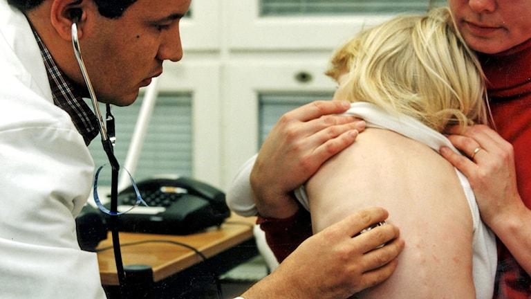 En läkare lyssnar på ett litet barns lungor.
